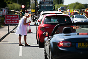 A woman in white hand out leaflets about the dangers of fracking to waiting traffic in New Preston Road, Lancashire, United Kingdom, June 29th 2018.  Block Around the Clock - a fourty eight hours of event with work shops, yoga, sleeping and anti-fracking campaigning in front of the gates to Cuadrillas fracking site in Lancashire. The event was organised by anti-fracking campaigners in spite of an injunction granted to Cuadrilla to prevent protest against the impending shale gas exploitation. The Cuadrilla site in Lancashire in a highly contested site, almost ready to drill for gas.
