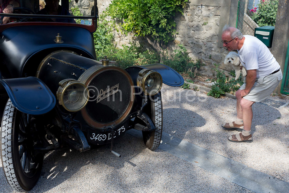 A local frenchman and his pet dog admires a visiting 1912 Delauney Belleville vintage car in a French village, during a three-day rally journey through the Corbieres wine region, on 26th May, 2017, in Lagrasse, Languedoc-Rousillon, south of France. Lagrasse is listed as one of Frances most beautiful villages and lies on the famous Route 20 wine route in the Basses-Corbieres region dating to the 13th century.