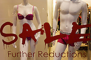 Sale sign and mannequins in London's Long Acre (street)clothing shop window.