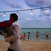 Man selling flowers walking past swimmersl on a beach at Playa del Carmen, Mexico