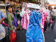 "04 FEBRUARY 2016 - BANGKOK, THAILAND:  A person selling Chinese New Year dresses from a handcart walks down Yaowarat Road in Bangkok's Chinatown district, before the celebration of the Lunar New Year. Chinese New Year, also called Lunar New Year or Tet (in Vietnamese communities) starts Monday February 8. The coming year will be the ""Year of the Monkey."" Thailand has the largest overseas Chinese population in the world; about 14 percent of Thais are of Chinese ancestry and some Chinese holidays, especially Chinese New Year, are widely celebrated in Thailand.     PHOTO BY JACK KURTZ"