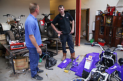 Man with Cerebral Palsy working as mechanic; talking to colleague in workshop,