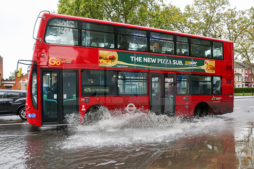 © Licensed to London News Pictures. 17/10/2019. London, UK. A bus drives through a flood on Tottenham High Road after heavy downpour in north London this afternoon. Photo credit: Dinendra Haria/LNP
