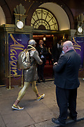 An eccentric man dressed in gold strides past theatre staff outside the Prince Edward Street in London's Soho, on 19th October 2017, in London, England.