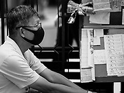 "14 JANUARY 2019 - BANGKOK, THAILAND: A man wearing dust filter breathing mask sells lottery tickets in central Bangkok. Bangkok has been blanketed by heavily polluted air for almost a week. Monday morning, the AQI (Air Quality Index) for Bangkok  was 182, worse than New Delhi, Jakarta, or Beijing. The Saphan Kwai neighborhood of Bangkok recorded an AQI of 370 and the Lat Yao neighborhood recorded an AQI of 403. An AQI above 50 is considered unsafe. Public health officials have warned people to avoid ""unnecessary"" outdoor activities and wear breathing masks to filter out the dust.     PHOTO BY JACK KURTZ"