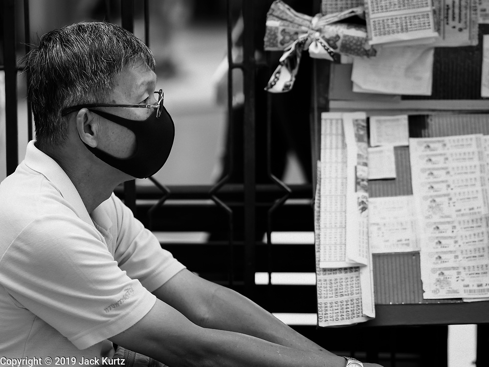 """14 JANUARY 2019 - BANGKOK, THAILAND: A man wearing dust filter breathing mask sells lottery tickets in central Bangkok. Bangkok has been blanketed by heavily polluted air for almost a week. Monday morning, the AQI (Air Quality Index) for Bangkok  was 182, worse than New Delhi, Jakarta, or Beijing. The Saphan Kwai neighborhood of Bangkok recorded an AQI of 370 and the Lat Yao neighborhood recorded an AQI of 403. An AQI above 50 is considered unsafe. Public health officials have warned people to avoid """"unnecessary"""" outdoor activities and wear breathing masks to filter out the dust.     PHOTO BY JACK KURTZ"""