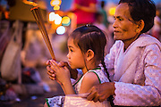 """30 JANUARY 2013 - PHNOM PENH, CAMBODIA:    A Cambodian girl and her grandmother pray for late Cambodian King Norodom Sihanouk in Phnom Penh.  Sihanouk (31 October 1922- 15 October 2012) was the King of Cambodia from 1941 to 1955 and again from 1993 to 2004. He was the effective ruler of Cambodia from 1953 to 1970. After his second abdication in 2004, he was given the honorific of """"The King-Father of Cambodia."""" Sihanouk held so many positions since 1941 that the Guinness Book of World Records identifies him as the politician who has served the world's greatest variety of political offices. These included two terms as king, two as sovereign prince, one as president, two as prime minister, as well as numerous positions as leader of various governments-in-exile. He served as puppet head of state for the Khmer Rouge government in 1975-1976. Most of these positions were only honorific, including the last position as constitutional king of Cambodia. Sihanouk's actual period of effective rule over Cambodia was from 9 November 1953, when Cambodia gained its independence from France, until 18 March 1970, when General Lon Nol and the National Assembly deposed him. Upon his final abdication, the Cambodian throne council appointed Norodom Sihamoni, one of Sihanouk's sons, as the new king. Sihanouk died in Beijing, China, where he was receiving medical care, on Oct. 15, 2012. His cremation is scheduled to take place on Feb. 4, 2013. Over a million people are expected to attend the service.        PHOTO BY JACK KURTZ"""