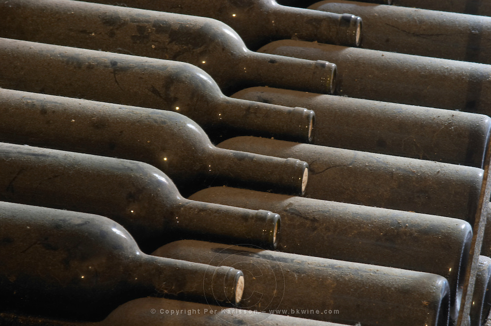 Piles of old bottles aging in the cellar, detail of dusty old bottles in diagonal Chateau Vannieres (Vannières) La Cadiere (Cadière) d'Azur Bandol Var Cote d'Azur France