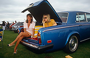 In a grass-covered car park, two ladies sit in the boot of a shining blue Rolls-Royce, chatting and sipping Champagne from crystal glasses by an unseen male friend during the day at Royal Ascot horse racing week. Surrounded by other cars and members of high-society who have congregated on this part of southern England, they are dressed in the fashion of the era, one of the girls' with her long bare legs dangling from the cover of this luxury car. car. The day is overcast, with threatening clouds behind the party but despite this, they are in a bubbly and excitable mood. Royal Ascot is held every June and is one of the main dates on the sporting calendar and social season.