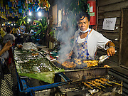 25 SEPTEMBER 2016 - BANGKOK, THAILAND: A grilled meat vendor cooks chicken, squid and fish before a Likay performance in Pom Mahakan Fort. The performance was to support residents of the old fort, who are fighting eviction orders by the city of Bangkok. City officials have made repeated attempts to evict people since Sept 3, 2016, but about 44 families are still living in the community. Likay is a form of popular folk theatre from Thailand. It uses a combination of extravagant costumes, barely equipped stages and vague storylines. The performances depend mainly on the actors' skills of improvisation and the audiences' imagination. There used to be several Likay troupes based in the old fort, but they left the community more than 50 years ago. The troupe that performed Sunday night was an amateur troupe comprised of college students and office workers.      PHOTO BY JACK KURTZ