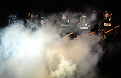 CMPD officers stand in a haze of tear gas on Old Concord Rd. on Tuesday night, Sept. 20, 2016 in Charlotte, N.C. The protest began on Old Concord Road at Bonnie Lane, where a Charlotte-Mecklenburg police officer fatally shot a man in the parking lot of The Village at College Downs apartment complex Tuesday afternoon. The man who died was identified late Tuesday as Keith Scott, 43, and the officer who fired the fatal shot was CMPD Officer Brentley Vinson. Photo by Jeff Siner/Charlotte Observer/TNS/ABACAPRESS.COM