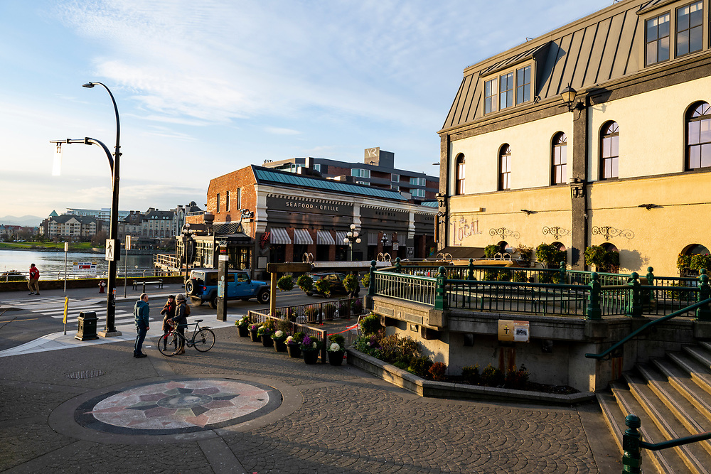 Victoria, British Columbia, Canada - February 10, 2020: Three people talk on a sunny winter afternoon at the intersection of Wharf Avenue and Bastion Square in Victoria, BC.