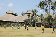 """Boys and girls students playing football during break with 'Heart of School in background'<br /><br />The Green School (Bali) is one of a kind in Indonesia. It is a private, kindergarten to secondary International school located along the Ayung River near Ubud, Bali, Indonesia. The school buildings are of ecologically-sustainable design made primarily of bamboo, also using local grass and mud walls. There are over 600 students coming from over 40 countries with a percentage of scholarships for local Indonesian students.<br /><br />The impressive three-domed """"Heart of School Building"""" is 60 metres long and uses 2500 bamboo poles. The school also utilizes renewable building materials for some of its other needs, and almost everything, even the desks, chairs, some of the clothes and football goal posts are made of bamboo.<br /><br />The educational focus is on ecological sustainability. Subjects taught include English, mathematics and science, including ecology, the environment and sustainability, as well as the creative arts, global perspectives and environmental management. This educational establishment is unlike other international schools in Indonesia. <br /><br />Renewable energy sources, including solar power and hydroelectric vortex, provide over 50% of the energy needs of the school. The school has an organic permaculture system and prepares students to become stewards of the environment. <br /><br />The school was founded by John and Cynthia Hardy in 2008."""