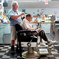 Wilford Ellison gets a haircut from barber Ray Rivenbark at the Ideal Barber shop in Burgaw, N.C. Thursday, Aug. 27, 2009. A new super-sized Walmart opening near BUrgaw may pose competition for area merchants. Photo By Mike Spencer/STAR-NEWS