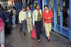 Single mothers walking through town centre with teenage children,