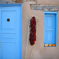 North America, USA, New Mexico. Adobe Blue Door and Hanging Chilis