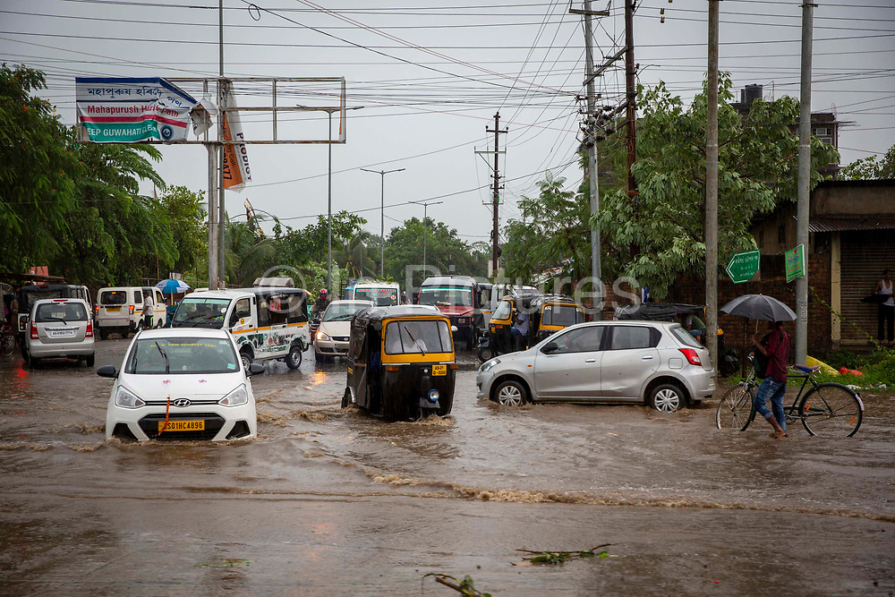 Cars, rickshaws, vans and bicycles drive through flooded streets after a heavy rainfall on Route 27 on 20th September 2018 in Guwahati, Assam, India.