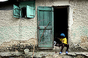 A young boy begins to eat his dinner sitting on the threshold of his families home high on the mountainside above Carrefour, Haiti.  Malnutricion is prevalent throughout Haiti, due to the lack of food and the monotony in their meal structures.