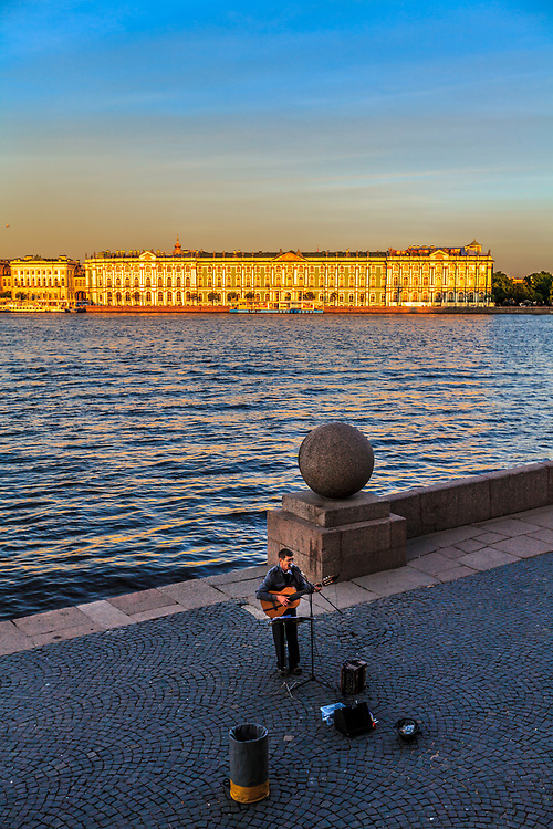 A guitarist  performes his song on the Vasilyevsky island in St Petersburg, Russia. The Winter Palace which was the official residence of the Russian monarchs is seen on the other side of Neva River.