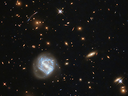 May 25, 2018 - Space - Image Released Today: At first glance, this image is dominated by the vibrant glow of the swirling spiral to the lower left of the frame on May 21st. However, this galaxy is far from the most interesting spectacle here, behind it sits a galaxy cluster. Galaxies are not randomly distributed in space; they swarm together, gathered up by the unyielding hand of gravity, to form groups and clusters. The Milky Way is a member of the Local Group, which is part of the Virgo Cluster, which in turn is part of the 100,000-galaxy-strong Laniakea Supercluster. The galaxy cluster seen in this image is known as SDSS J0333+0651. (Credit Image: ? ESA/NASA via ZUMA Wire/ZUMAPRESS.com)