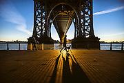 A jogger passes down the Williamsburg Bridge at sunrise, New York