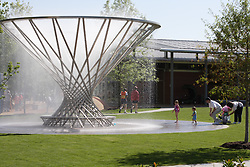 Stock photo of young children enjoying the Mist Tree fountain on a hot afternoon