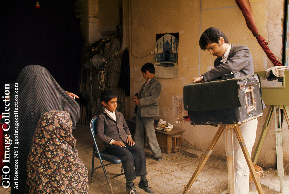 In the Isfahan bazaar a boy sits stiffly for his photograph.