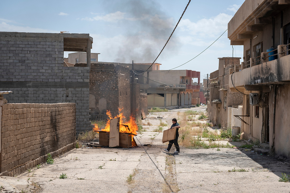 On October 19, 2016, ISIS was pushed out of the predomately Christian town of Qaraqosh, ending its destructive two-year occupation. In the months that followed, a trickle of residents began to return, cleaning up the damage to their homes. In this image, a man carries ruined items out of a home to be burned. (May 5, 2017)