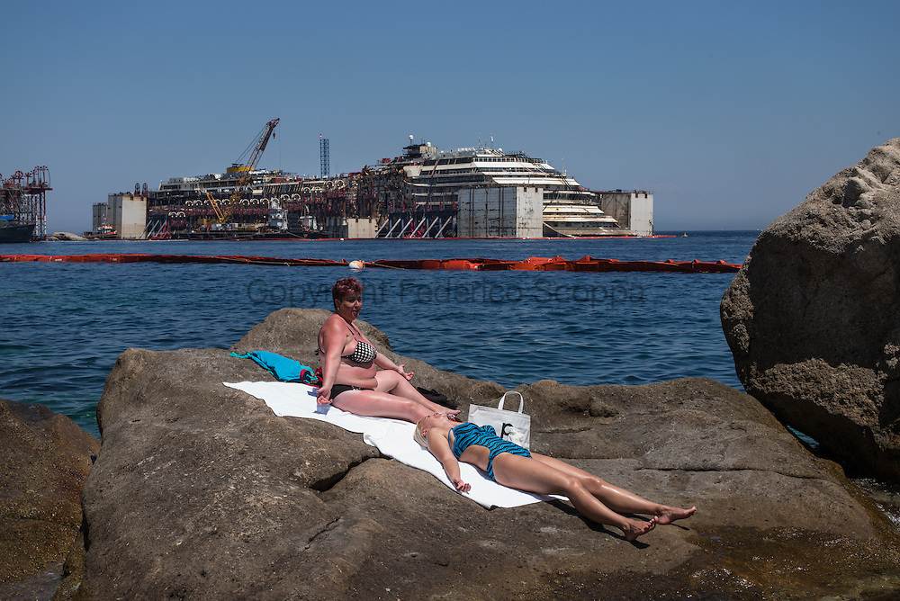 Re float operation goes one very slowly, two women are seen sunbathing on the Giglio island coast