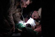 Corpsman Dustin Nietszke monitors the pulse while Marine Black Harruff listens to the heratbeat in an attempt to save the life of a small girl who had all of her limbs blown off by a Taliban improvised explosive device. The girl did not survive.