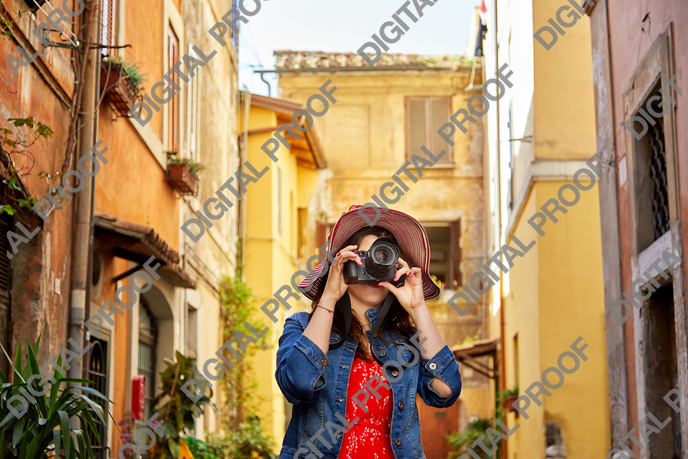 Unrecognizable tourist woman standing and focusing with camera at Trastevere in Rome, Italy.