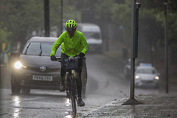 © Licensed to London News Pictures. 18/05/2021. London, UK. Cyclist is caught in the rain in Bromley, south London. Photo credit: Marcin Nowak/LNP
