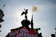 A young protestor stands on the statue of Eros and waves an Extinction Rebellion flag during a protest against climate change in the middle of Piccadilly Circus on 15th April, 2019 in London, United Kingdom.  Extinction Rebellion have blocked five central London landmarks in protest against government inaction on climate change. The youth group of Extinction Rebellion was based at Piccadilly Circus..