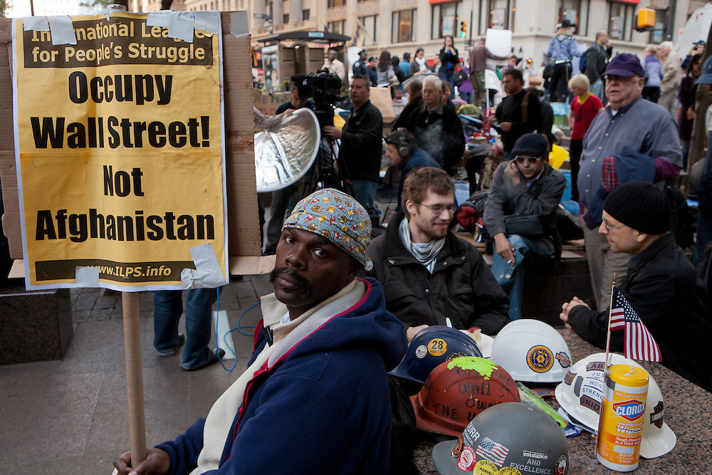 """A man sits at a table covered in hard hats, with a sign from the International League for People's Struggle that reads """"Occupy Wall Street! Not Afghanistan."""""""