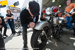 Willie G. Davidson signs a front fender during Wednesday's Ride-In Bike Show at the Harley-Davidson display during Daytona Bike Week. FL, USA. March 12, 2014.  Photography ©2014 Michael Lichter.