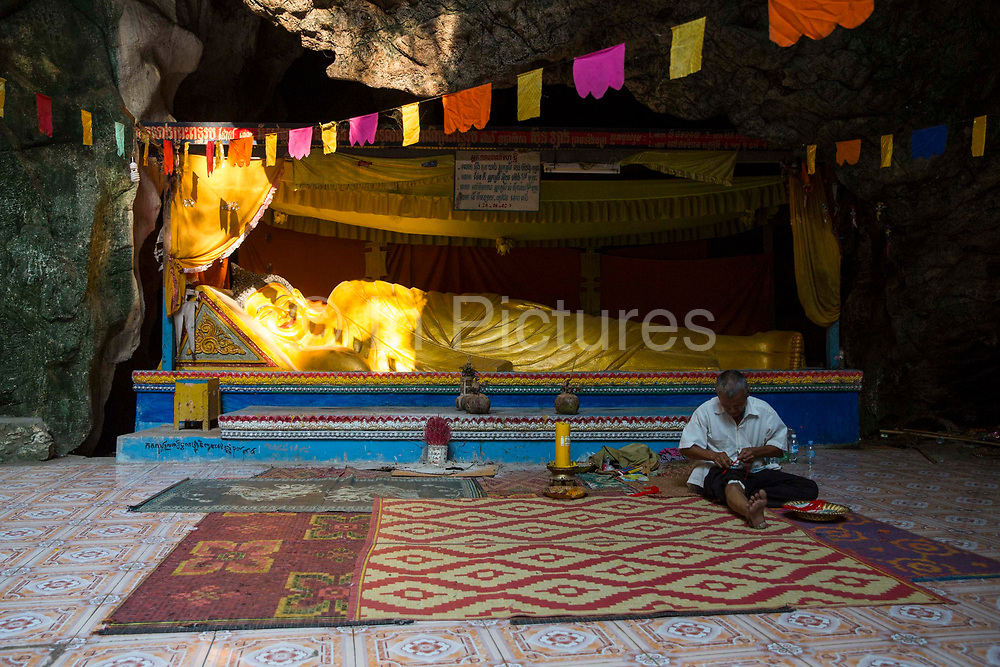 A golden reclining Buddha statue in the sunlight in a Killing Cave of Phnom Sampeau in Battambang region, Cambodia, South East Asia. The lying Buddha represents his last illness, about to enter the parinirvana after death. Many victims were killed and thrown into these caves during the Khmer Rouge in 1970s. A Cambodian man sits in front of the statue making wrist band souvenirs.
