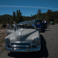 Members of a classic car club admire scenery in Wyoming's Yellowstone National Park.