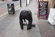 Man rolling up a mat in Whitechapel, London, UK.