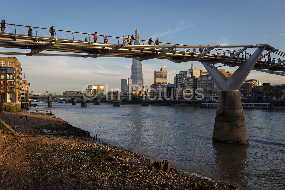 In late afternoon Autumn sunshine and with the tall point of the Shard skyscraper in the distance, pedestrians walk over the Millennium Bridge on the River Thames, on 30th October 2017, in the City of London, England.