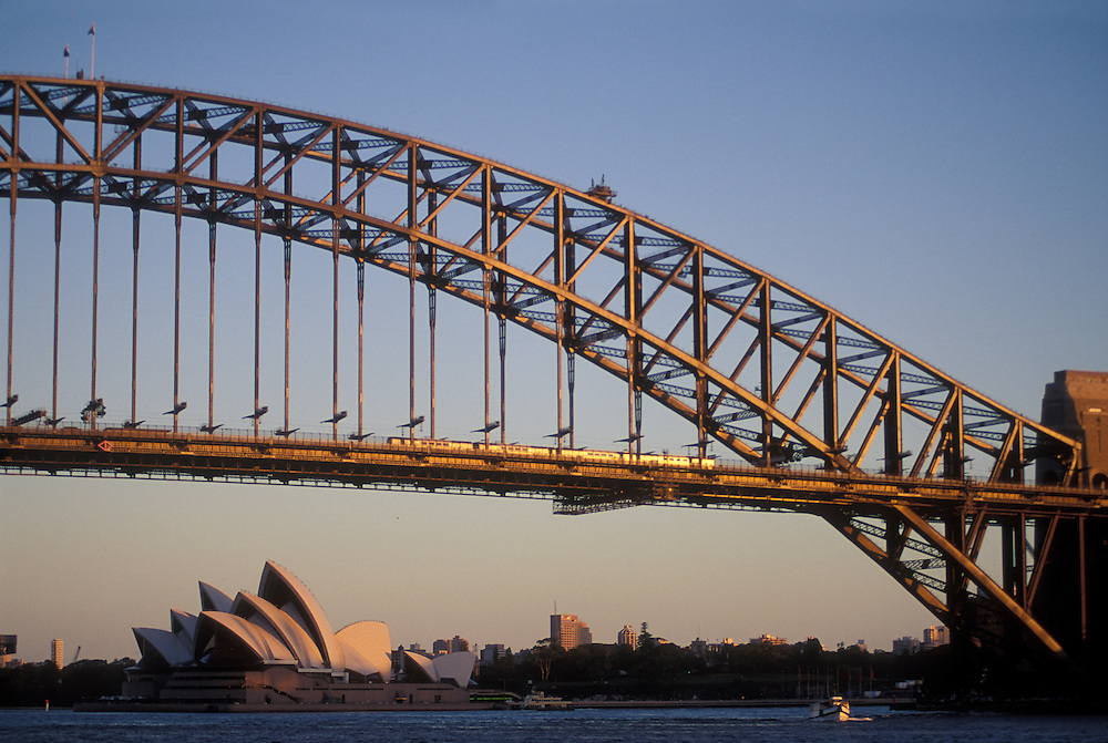 Australia, New South Wales, Setting sun lights Sydney Harbour Bridge and central business district seen from MacMahon Point