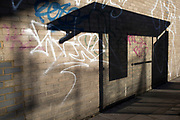 Bus shelter casts a shadow on a wall covered in graffiti in East London, UK. A very graphic pattern of light and dark.
