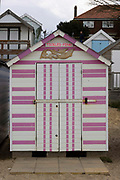 Tickled Pink! beach hut on a small island with sandy beaches the river Blackwater on 2nd May 2021 in Mersea Island, Essex, United Kingdom. It is the most eastern inhabited island in the UK, it has a total area of seven square miles, and a permanent population of around 7,000, though the islands holiday parks mean this population swells considerably in peak season. Its attached to mainland Essex by one solitary causeway.  Evolving from fishermens huts, boatsheds or Victorian bathing machines, beach huts, Small, wooden buildings, typically measuring 12ft by 10ft, often with rudimentary electricity but no plumbing, a beach hut may be a modest thing to look at, but it holds a countrys collective yearning at the seaside.