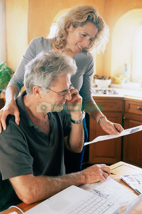Dec. 14, 2012 - Couple with laptop and paperwork (Credit Image: © Image Source/ZUMAPRESS.com)