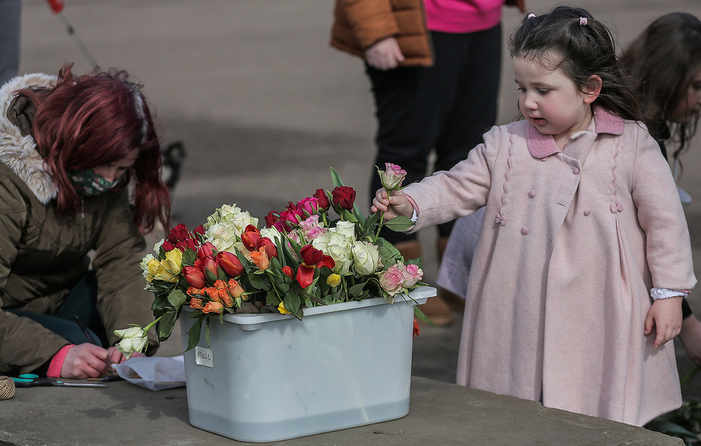 13th, March, 2021. Cheltenham, England. A member of the public picks a flower to lay in memory of Sarah Everard.