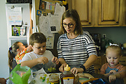 """GUNTERSVILLE, AL – SEPTEMBER 3, 2019: Brianna Barker, 34, prepares lunch for her children. As the founder of Huntsville's chapter of the International Cesarean Awareness Network (ICAN), Barker facilitates support meetings and moderates online forums on topics surrounding cesarean birth in an effort to support mothers seeking a vaginal birth after cesarean (VBAC). <br /> <br /> Barker's first child was born prematurely by cesarean. Reflecting on the birth of Callen, her second child, Barker recalls feeling alone in her effort to have a normal vaginal birth. """"It was really hard. I didn't have a doula or any support network. Even today I have recurring nightmares where I'm alone in a dark hospital in labor. In my subconscious, I was just so alone."""" With their third and fourth children the Barkers chose an out of hospital birth experience – driving 2 ½ hours to Tennessee for every prenatal appointment. During this time, Barker was involved in the fight to legalize midwifery in Alabama. """"I knew I had many privileges that many others didn't have. So I went to Montgomery. And the other mom's and I – we all have this collective PTSD from dragging our screaming babies around Montgomery, marching to hearings and all that, just so there would be accountability. It's incredible the amount of barriers to access for v-backs, but I was able to have a vaginal birth with Callen, and for that I'm so grateful."""" <br /> <br /> Although midwifery has been legalized in Alabama, from Barker's perspective """"the fight is not really over."""" Today, many hospitals still ban vaginal births after cesarean. """"There's just so much misinformation, even about what the guidelines are,"""" Barker says. """"They're essentially mandating surgery for a large percentage of their patients, and I don't want that for other people. I want to make a difference, so other mom's can have the same experience I had. And if enough moms and families come together with more information and more knowle"""