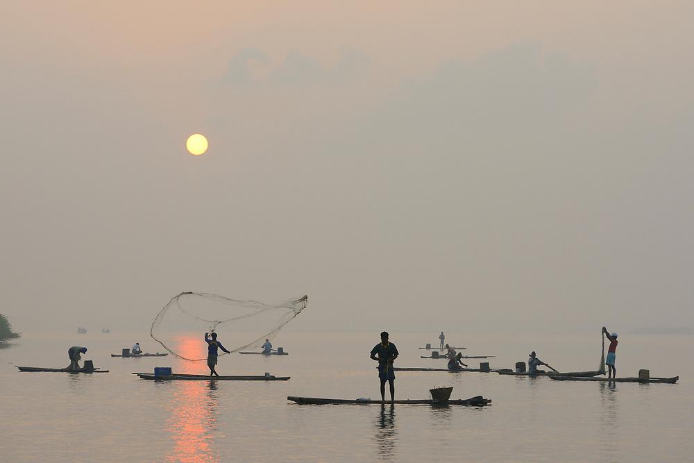 Fisherman throw net in a lake at sunrise, Pulicat Lake, Tamil Nadu, India