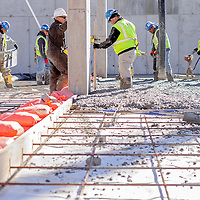 010814       Cable Hoover<br /> <br /> A construction crew pours and spreads concrete to form the parking area for the new Hooghan Hozho housing project in downtown Gallup Wednesday.