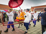 19 OCTOBER 2014 - BANG BUA THONG, NONTHABURI, THAILAND:  Attendants carry the presiding monk around the plaza on a sedan chair at Wat Bang Phai for Apiwan Wiriyachai's cremation in Bang Bua Thong, a Bangkok suburb, Sunday. Apiwan was a prominent Red Shirt leader. He was member of the Pheu Thai Party of former Prime Minister Yingluck Shinawatra, and a member of the Thai parliament and served as Yingluck's Deputy Prime Minister. The military government that deposed the elected government in May, 2014, charged Apiwan with Lese Majeste for allegedly insulting the Thai Monarchy. Rather than face the charges, Apiwan fled Thailand to the Philippines. He died of a lung infection in the Philippines on Oct. 6. The military government gave his family permission to bring him back to Thailand for the funeral. His cremation was the largest Red Shirt gathering since the coup.    PHOTO BY JACK KURTZ