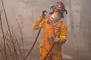 A firefighter retrieves a hose after his tanker ran out of water while battling the fire racing up the ravine towards CR 26 in Smith County on Wednesday.© 2011 Jaime R. Carrero/Tyler Morning Telegraph