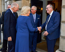 The Prince of Wales and the Duchess of Cornwall are greeted by Arthur Edwards (right) as they arrive to attend a tea party held at Spencer House in London to celebrate 70 inspirational people marking their 70th birthday this year.